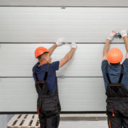 Two people installing roller shutter doors